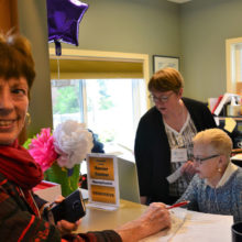 Sada Ross, left, gets help from Operations Manager Mary Gibbs, center, and Genevieve Moyer, at reception.
