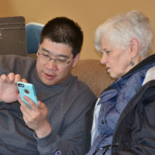 Suzanne gets a little help with her smart phone during Technology Tutoring.